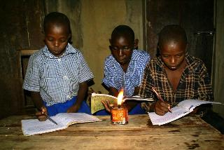 Children reading with kerosene lamp