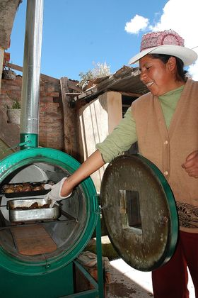 Peruvian Woman using an improved oven (by Fondesurco).